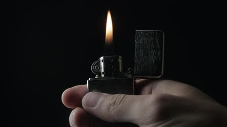 close-up of the opening and the burning of iron Zippo lighter on a black background Dostupné videozáznamy