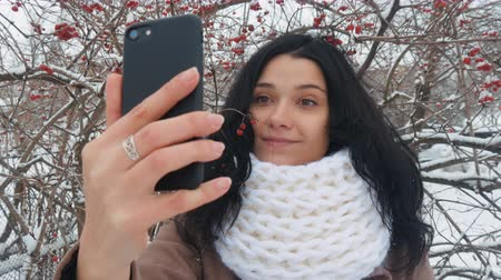 make photo : Young woman making selfie using smartphone in winter in snow park