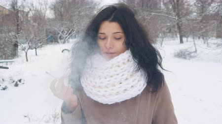 fumegante : young attractive woman smokes a cigarette in winter in a snow park