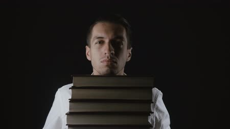 erudite : Young man in hands holds a pile of books Stock Footage