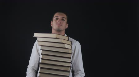 erudite : Young man takes up a pile of books. Businessman with books in hands.