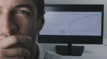 handlowiec : close-up face of a young businessman against the background of the trading schedule on the monitor.