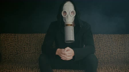 hazmat : Man in a gas mask sitting in smoke in a dark room. Stalker in the post-apocalyptic world