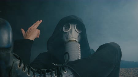 stalker : Man in a gas mask sitting in smoke in a dark room. Stalker in the post-apocalyptic world