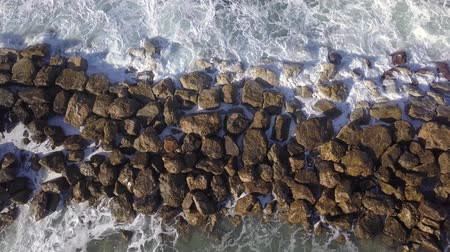 Ocean waves are breaking on a Breakwater at winter sea. Aerial top down view.