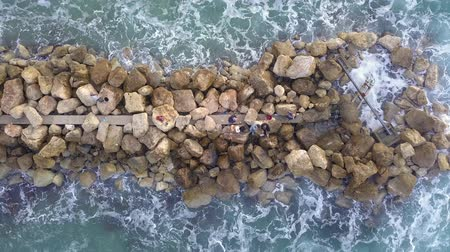 fisherman : Aerial view of a Fishermen are standing on a breakwater and waves crashing on the breakwater. Stock Footage