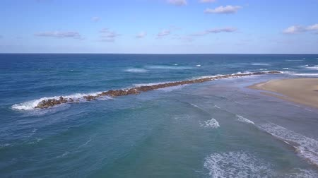 Aerial shot of sandy beach and Sea waves wash rough stones at break wall.