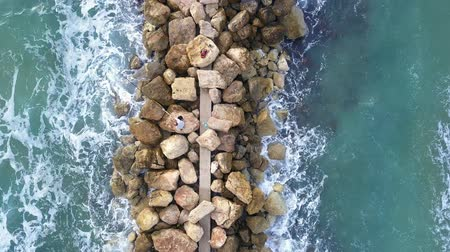 dalgakıran : Aerial view of a Fishermen are standing on a breakwater and waves crashing on the breakwater. Stok Video