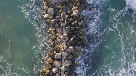 Aerial view of a Fishermen are standing on a breakwater. Dostupné videozáznamy