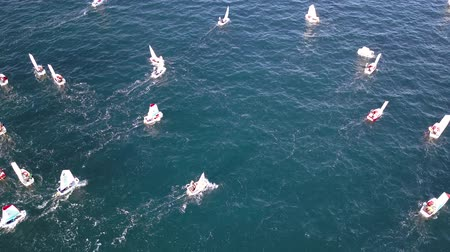 Group of small sail boats manoeuvring in a calm sea waters. Aerial view.
