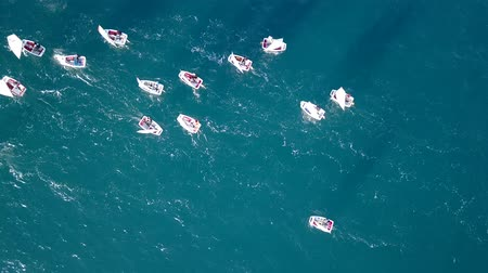 Against the current concept : Group of small sail boats manoeuvring in calm sea waters. Aerial view