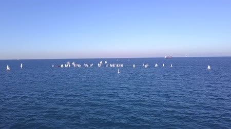 Aerial shot of approaching to a Group of small sail boats in calm sea waters.