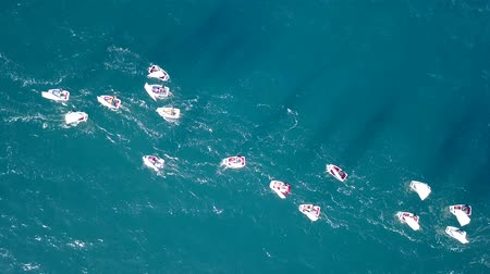 Against the Flow concept : Group of small sail boats manoeuvring in calm sea waters. Aerial view
