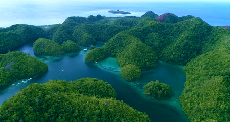 Aerial view flying over the beautiful and tropical green mountains Sugba Lagoon in Siargao, Philippines