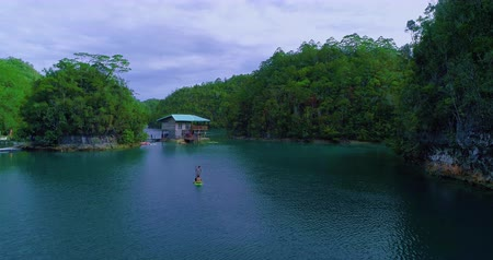 People on the board are swimming in the bay. Aerial view flying over the beautiful and tropical green mountains Sugba Lagoon in Siargao, Philippines Dostupné videozáznamy
