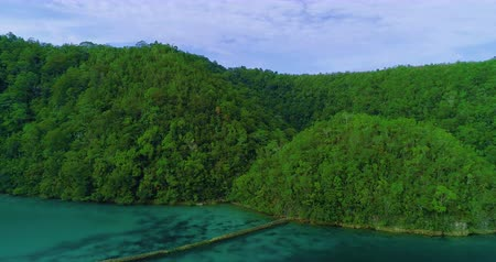 korall : Aerial view flying over the beautiful and tropical green mountains Sugba Lagoon in Siargao, Philippines