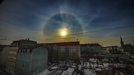 Spectacular Sun Halo Weather Timelapse Over A City 4K, a sun rise over a housing development.