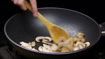 vegetable wok : Chopped slices of mushrooms and chicken fillets are fried in an oil in a wok pan. Part of the process of cooking with champignons in the home recipe. Close Stock Footage
