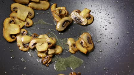 wok food : Chopped slices of mushrooms and chicken fillets are fried in an oil in a wok pan. Part of the process of cooking with champignons in the home recipe. Close Stock Footage