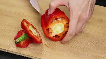 bolgár : Large red bell peppers are separated and the core is removed. The chef holds a knife in female hands and cuts a healthy vegetable.