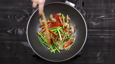 vegetable wok : Vegetables with peppers and garlic sprouts and sliced mushrooms with chicken fillet are fried in a wok pan. Cooking with champignons and fried noodles according to homemade recipe. Close