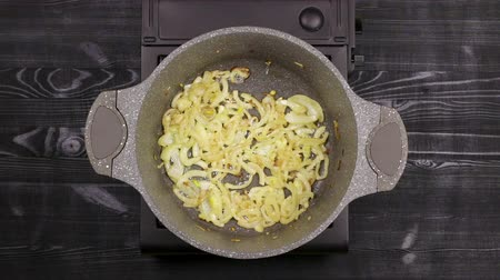 saute : Sliced onion pieces are roasted in a saucepan with a marble or stone non-stick coating to a golden brown color. Oil boils on the bottom. Top view