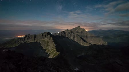 Mountains rising out of the shadows in the moonlight, in the background the Milky Way preserves the clouds 4K Time lapse