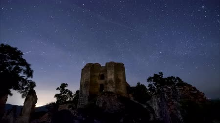Timelapse 4K Milky Way glows above the castle ruins.