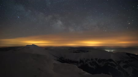 Timelapse 4K Rise Milky Way glows above mountain landscape in winter, rotation to the right