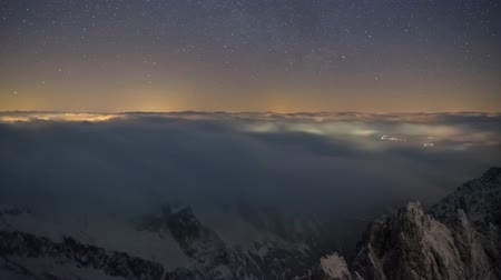Timelapse 4K Clouds Cover The Landscape High In The Mountains, Under A Night Sky Full Of Stars.