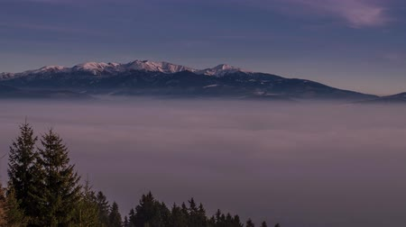 outlook : inversion clouds flying through the valley in the background behind the towering mountains 4K Time Lapse