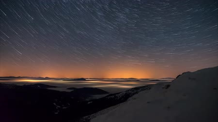 4K Time Lapse Startrails will rotate in the sky over a night landscape veiled inverse cloud