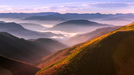 flowing fog in the valleys at sunrise illuminated landscape east of the sun 4K Time Lapse