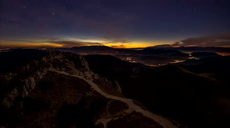 After sunrise, the night sky over the mountain landscape changes into daytime scenery with clouds Dostupné videozáznamy