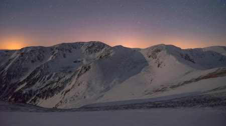 4k timelapse East of the moon will illuminate the high mountains in the winter under the night sky