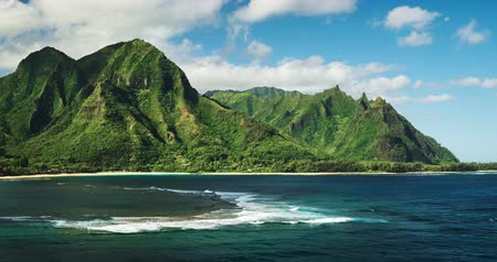 paraíso : Aerial view flying over tropical coral reef and breaking ocean waves towards beautiful green mountains on Kauai Vídeos