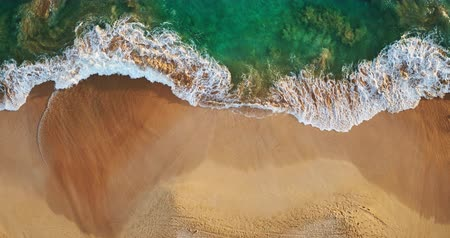 árapály : Aerial view waves break on white sand beach at sunset