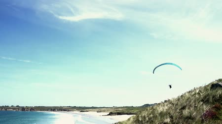 bretagne : Le Conquet, Finistere  France - 22 August, 2019: extreme athlete paraglider enjoys flying along the beach and shore of the Brittany coast during a strong onshore wind