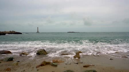 view of the Cap de La Hague ligthhouse with waves gently breaking on the beach