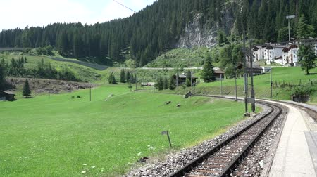 Arosa, GR  Switzerland - 24 July, 2019: the red Rhaetian Railway train arrives at the Litzirueti train station in the Swiss Alps near Arosa