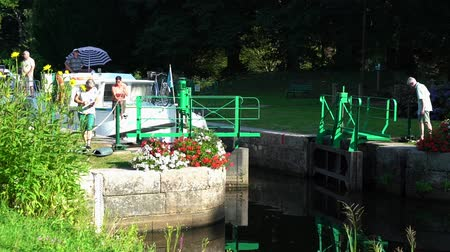bretagne : Josselin, Brittany  France - 25 August, 2019: houseboat travelllers opening a river lock on the riverboat canals of northwestern France in Brittany
