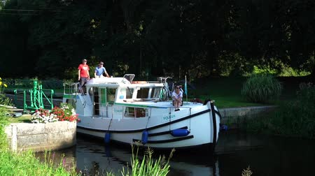 bretagne : Josselin, Brittany  France - 25 August, 2019: houseboat travelllers passing through a river lock on the riverboat canals of northwestern France in Brittany