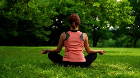 girl sitting in the lotus position on the grass in the park