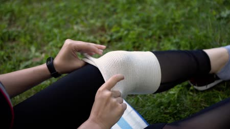 girl puts a bandage on her knee in nature