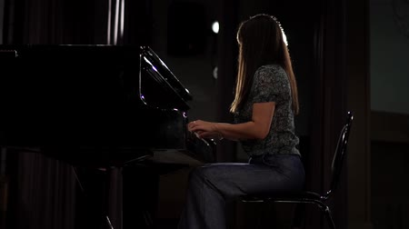 girl playing the piano in the concert hall