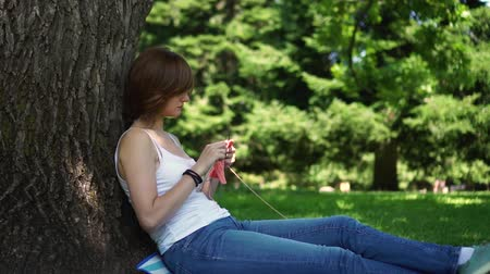 young girl doing knitting in the park under a tree