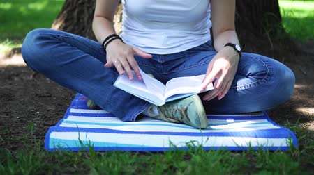 girl sitting in the park reading a book