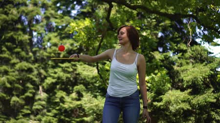 girl beats a racket on the ball in the park