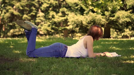 girl lying on the grass in the park and reading a book Stok Video