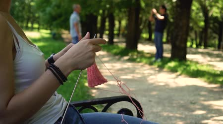 young girl doing knitting in the park on the bench